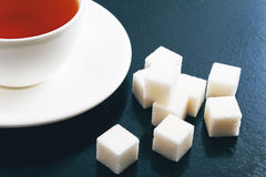 Taza de té y de azúcar de terrón en un fondo azul Foto de archivo