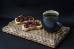 Taza de té y de bocadillo con el atasco Foto de archivo libre de regalías