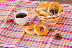 Taza de té y de buñuelo en una servilleta en una jaula Imagenes de archivo