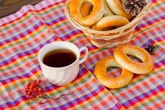 Taza de té y de buñuelo en una servilleta en una jaula Foto de archivo
