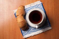 Taza de té y de cruasanes foto de archivo