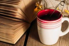 Taza de té y de libro abierto Fotografía de archivo libre de regalías