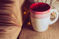 Taza de té y de libro abierto Imagen de archivo
