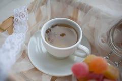 Taza de té y de mermelada en una endecha del tarro en el carro cubierto con un paño de seda blanco imágenes de archivo libres de regalías