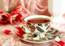 Taza de té y de tulipanes rosados Imagenes de archivo