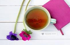 Taza de té y flores con el cuaderno rosado Fotografía de archivo libre de regalías