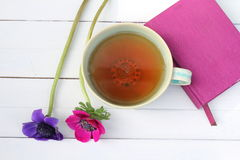 Taza de té y flores con el cuaderno rosado Fotos de archivo libres de regalías