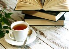 Taza de té y libros en de madera Imagen de archivo libre de regalías
