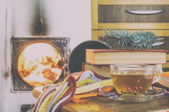 Taza de té y llamas del fuego en una chimenea Imagen de archivo