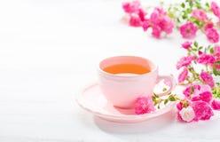 Taza de té y rama de pequeñas rosas rosadas en la tabla rústica blanca imagen de archivo libre de regalías