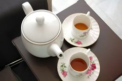 Taza de té y tetera blancas en silla marrón fotografía de archivo