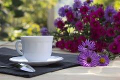 Taza de té y un ramo de flores carmesís y púrpuras Imagen de archivo
