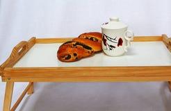 Taza de té y un rollo con las semillas de amapola en una pequeña tabla en cama Fotografía de archivo