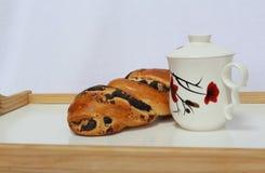 Taza de té y un rollo con las semillas de amapola en una pequeña tabla en cama Foto de archivo libre de regalías