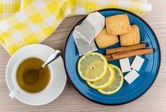 Taza de té caliente, azúcar, palillos de canela, rebanadas de limón Foto de archivo