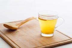 Taza de té con el limón y la cuchara de madera Foto de archivo libre de regalías