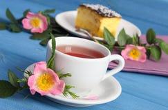 Taza de té con el pastel de queso y la flor color de rosa salvaje en tableros azules Fotografía de archivo libre de regalías