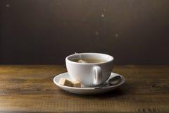 Taza de té con la bolsita de té en el platillo Foto de archivo libre de regalías