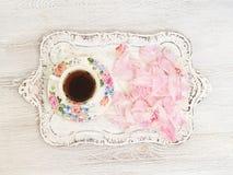 Taza de té con los pétalos de la peonía Fotos de archivo libres de regalías