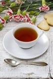 Taza de té y de pequeñas tortas Foto de archivo