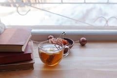 Taza de t? y libros en el travesa?o de madera de la ventana El concepto de lectura, fin de semana casero acogedor, relaja, ama le fotos de archivo