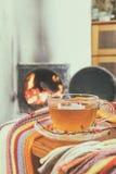 Taza de té y llamas del fuego en una chimenea Foto de archivo