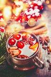 Taza de vino reflexionado sobre con las especias en el fondo festivo de la Navidad con el bokeh Fotos de archivo libres de regalías