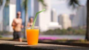 Taza de zumo de naranja fresco con el grupo corriente de la aptitud desconocida en parque de la ciudad Concepto de la forma de vi metrajes