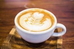 Taza del arte del Latte en la placa de madera Fotografía de archivo libre de regalías