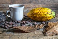 Taza del cacao y fruta del cacao en la tabla de madera foto de archivo