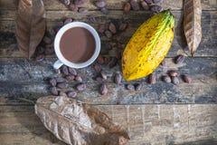 Taza del cacao y fruta del cacao en la tabla de madera imagenes de archivo