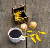 Taza del café, ataúd abierto con una flor, lazo dos de galletas Fotos de archivo