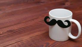 Taza del café con leche con el bigote en la tabla de madera Fotos de archivo libres de regalías