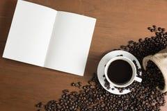 Taza del café con leche con el cuaderno en blanco imagenes de archivo