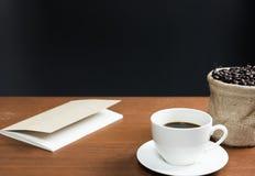 Taza del café con leche con el grano de café y el fondo negro imágenes de archivo libres de regalías