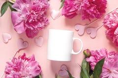 Taza del café con leche con las peonías y los corazones en fondo rosado Imagen de archivo