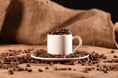Taza del café con leche con los granos de café imagen de archivo