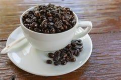 Taza del café con leche de los granos de café imagenes de archivo