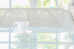 Taza del café con leche en la tabla con el fondo del travesaño de la ventana Imágenes de archivo libres de regalías