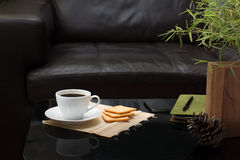 Taza del café con leche en la tabla de cristal en sala de estar Foto de archivo libre de regalías