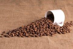 Taza del café con leche en tela texturizada por completo del grano del aroma, habas Foto de archivo