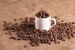 Taza del café con leche en tela texturizada por completo del grano del aroma, habas foto de archivo libre de regalías