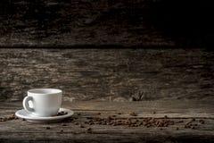 Taza del café con leche en una placa colocada en un ingenio rústico de los tableros de madera Imagen de archivo