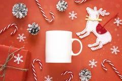 Taza del café con leche con las decoraciones de la Navidad en fondo rojo Foto de archivo