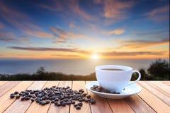 Taza del café con leche y granos de café en la tabla de madera y la vista de soles fotografía de archivo