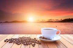 Taza del café con leche y granos de café en la tabla de madera y la vista de soles fotografía de archivo libre de regalías