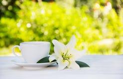 Taza del café con leche y lirio blanco en la tabla Pureza y dulzura Café de la mañana en el jardín Copie el espacio foto de archivo libre de regalías