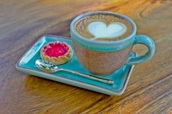Taza del café, forma del corazón con la galleta de la fresa en el backg de madera Foto de archivo libre de regalías