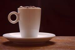 Taza del café express por completo de habas Imagen de archivo libre de regalías