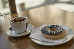 Taza del chocolate caliente con un buñuelo cubierto con el chocolate sobre una tabla de madera Imagen de archivo